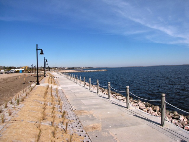 Beach walkway with lamp posts and rope guard rail overlooking water