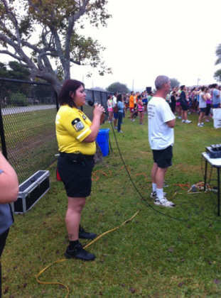 A woman in a yellow shirt and black pants talkin on a microphone to a crowd