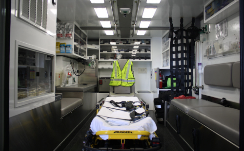 Inside the cab of an ambulance with a stretcher in the middle and equipment in storage