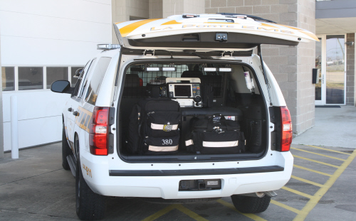 Inside the trunk of an EMS Suburban with medic bags and equipment