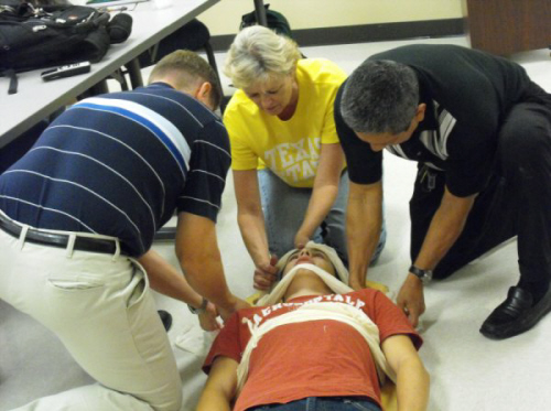 3 people practicing bracing a person on the floor with bandages on his chest and head