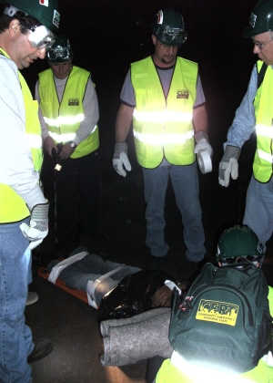 A group of men with green safety vests standing around safety gear
