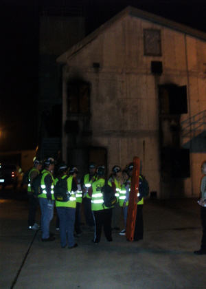 A group of people with green safety vests standing outside at night next to an old, rundown building