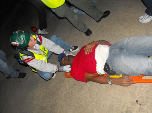 A woman practicing geting an unconscious man onto a transport board
