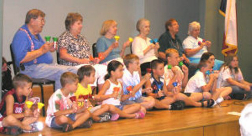 A group of senior citizens and children playing handbells